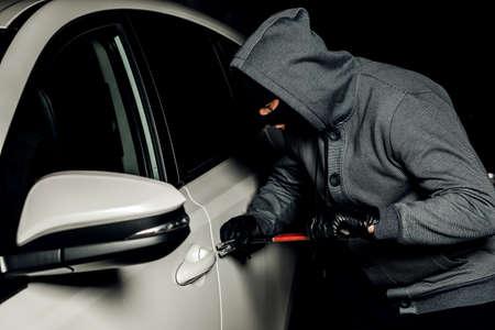 ladrón va a abrir la puerta del coche con una palanca