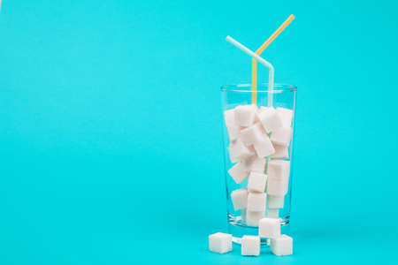 Glass of sugar. The concept of junk food. On red background