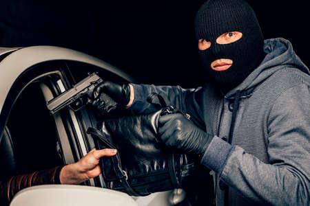 Un voleur masqué avec une arme à feu menace une femme dans une voiture. vol.