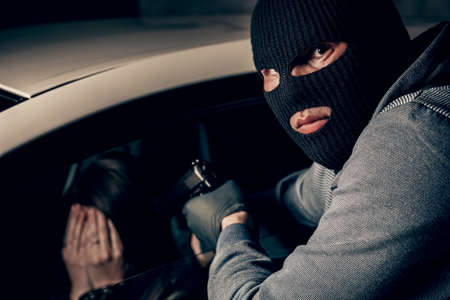 A masked robber with a gun threatens a woman in a car. robbery.
