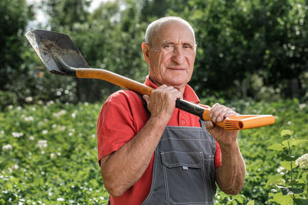 An adult male farmer posing with a shovel in the background of the farm