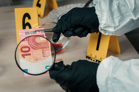 The criminalist is considering a magnifying glass shackle Euro bill at the crime scene.