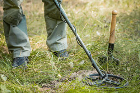 Man with electronic metal detector device, outdoor background.