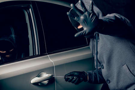 A man with a Balaclava on his head tried to break into the car. He uses a screwdriver. Hijacker, the concept of car theft Banco de Imagens - 131711564