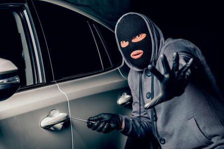 A man with a Balaclava on his head tried to break into the car. He uses a screwdriver. Hijacker, the concept of car theft Banco de Imagens