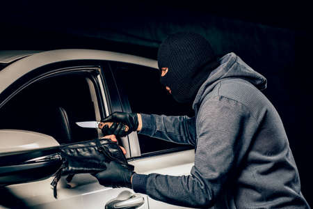 The robber in Balaclava threatening with a knife takes away a bag from the driver of a car. The concept of crime