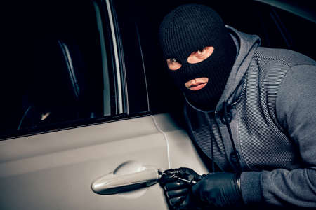 A man with a Balaclava on his head tried to break into the car. He uses a screwdriver. Hijacker, the concept of car theft Stockfoto