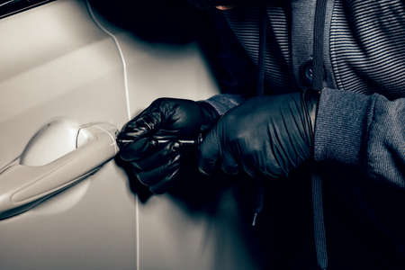 A man with a Balaclava on his head tried to break into the car. He uses a screwdriver. Hijacker, the concept of car theft Banco de Imagens - 131711655