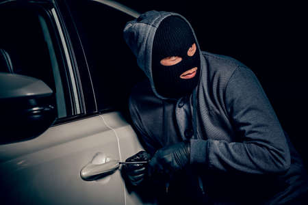 A man with a Balaclava on his head tried to break into the car. He uses a screwdriver. Hijacker, the concept of car theft Banco de Imagens - 131711658