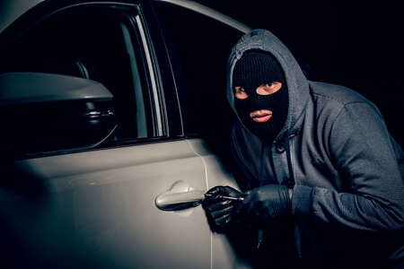 A man with a Balaclava on his head tried to break into the car. He uses a screwdriver. Hijacker, the concept of car theft Banco de Imagens - 131711659