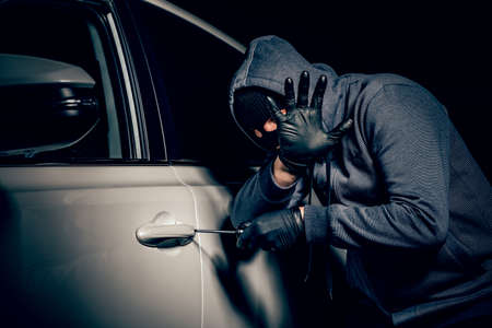 A man with a Balaclava on his head tried to break into the car. He uses a screwdriver. Hijacker, the concept of car theft Reklamní fotografie