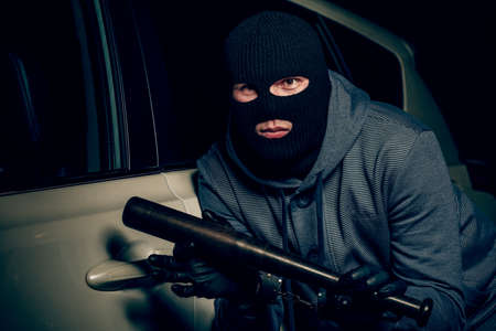 robber in a Balaclava tries to break the car glass with a baseball bat Reklamní fotografie