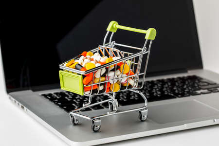 Online shopping and e-Commerce. Basket and laptop on white background Banco de Imagens