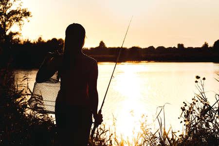 Silhouette einer Frau bei Sonnenuntergang mit einer Angelrute am Teich