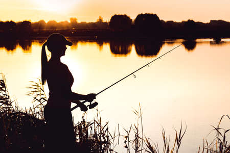 Silhouette of a woman at sunset with a fishing rod near the pond