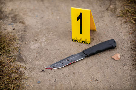 Crime scene investigation, bloody knife with crime markers on the ground, evidence of murder. Stock fotó - 131712972