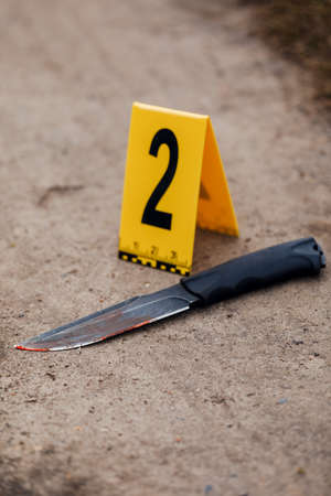Crime scene investigation, bloody knife with crime markers on the ground, evidence of murder. Stock fotó - 131712995