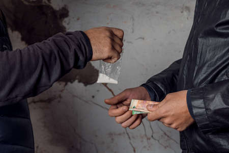 A person with money buys a dose of cocaine or heroin or other drug from a drug dealer.
