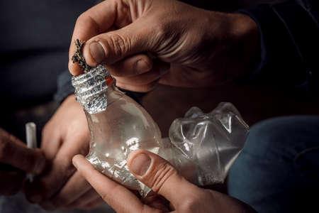 A man smokes drugs through a Bong bottle, a way of using cannabis