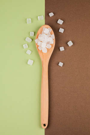 Sugar-replacing pills on a wooden spoon on green-brown backdrop of