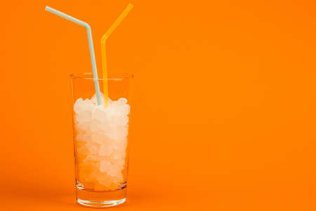 A glass of sugar cubes-the concept of unhealthy eating. On an orange background.