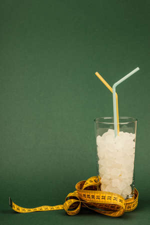 A glass of sugar cubes with a yellow measuring tape, the concept of unhealthy eating. On green background.