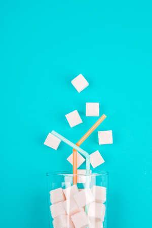 vol glas geraffineerde suiker op een blauwe achtergrond Stockfoto
