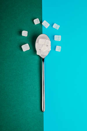 Sugar-replacing tablets with a spoon on a green and blue background. 版權商用圖片