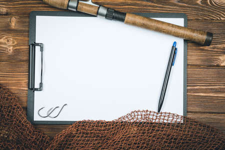 Fishing tackle-fishing, pen, hooks, wooden background.