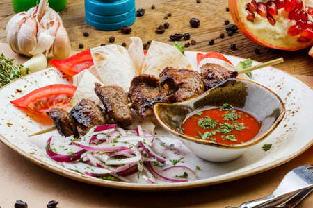 pork kebabs on a plate with sauce on a wooden table.