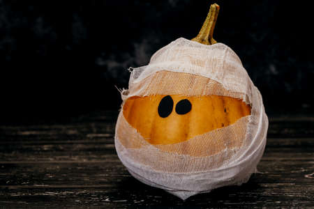 Zombie pumpkins in bandages, on a dark background. The concept of Halloween.