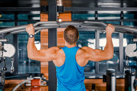 Professional athlete performs exercises in the gym. Exercise for the development of back muscles