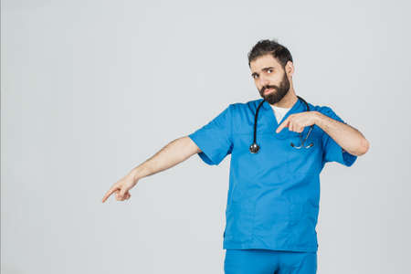 Portrait of doctor in blue uniform with his thumbs up. Isolated over white background people, medicine and healthcare. Stock fotó