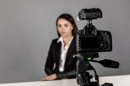 A woman makes a video for her blog using a tripod mounted digital camera.