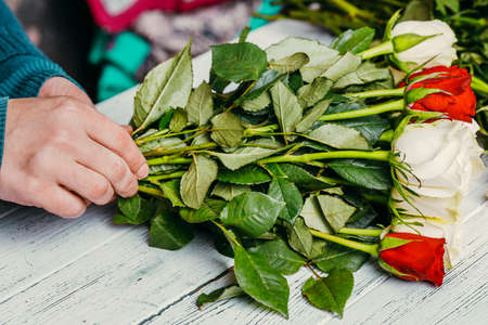 Florist at work makes a fashionable modern bouquet of different flowers Banco de Imagens