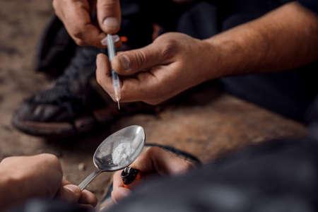 Two shabby  men preparing drug injection in slums.