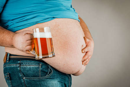 A man with a fat belly holding a glass of beer. On gray background