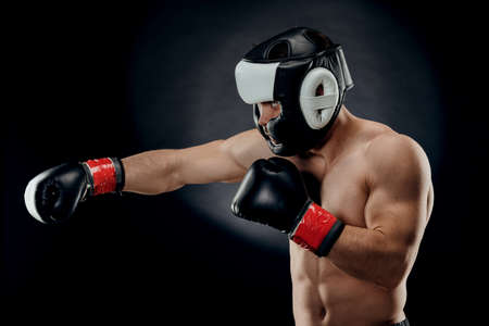 Portrait of a young man with a Boxing helmet and gloves on a dark background