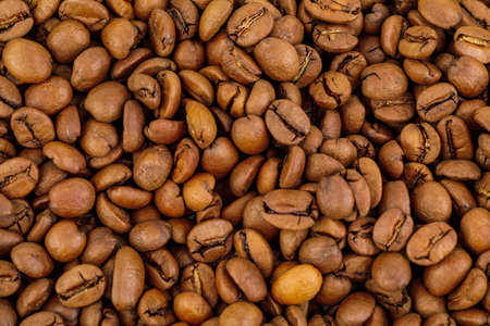 Black coffee beans close-up, background.