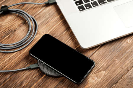 Wireless charging lies next to the computer on a stylish wooden table.