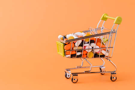 Pills and shopping cart on a yellow background Concept of buying drugs, prices for treatment. Sale in the pharmacy 版權商用圖片
