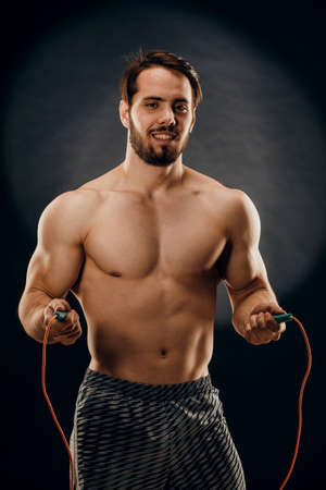 A handsome male bodybuilder with a rope in his hands on a dark background