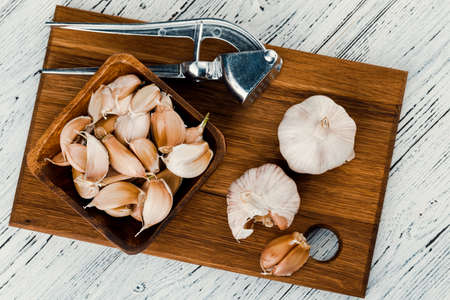 Garlic on a rustic table in a wooden bowl. Fresh peeled garlic