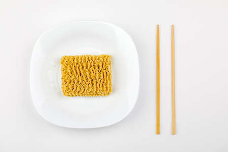 dry instant noodle on plate with chopsticks isolated on white background.