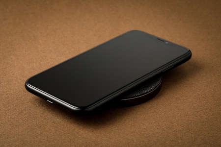 The smartphone is charged by a wireless charger  Concept of new technologies