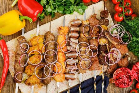 brochettes avec différentes sortes de viande avec oignon et pâte.