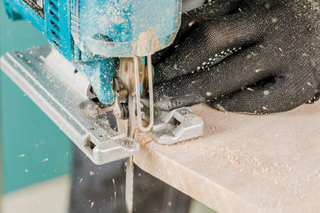 The worker cuts the boards with an electric jigsaw, the dust flies in all directions. The concept of construction and repair