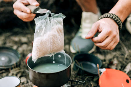 Tourist eats food in the summer forest. Outdoor recreation