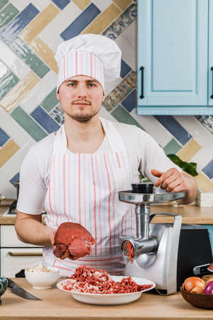 Raw meat. The process of preparing minced meat is carried out using a meat grinder. A male chef uses a meat grinder in the kitchen