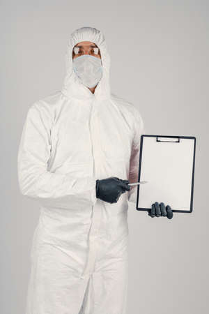 A man in a uniform and face mask holding a placard. Concept of healthcare and medicine.